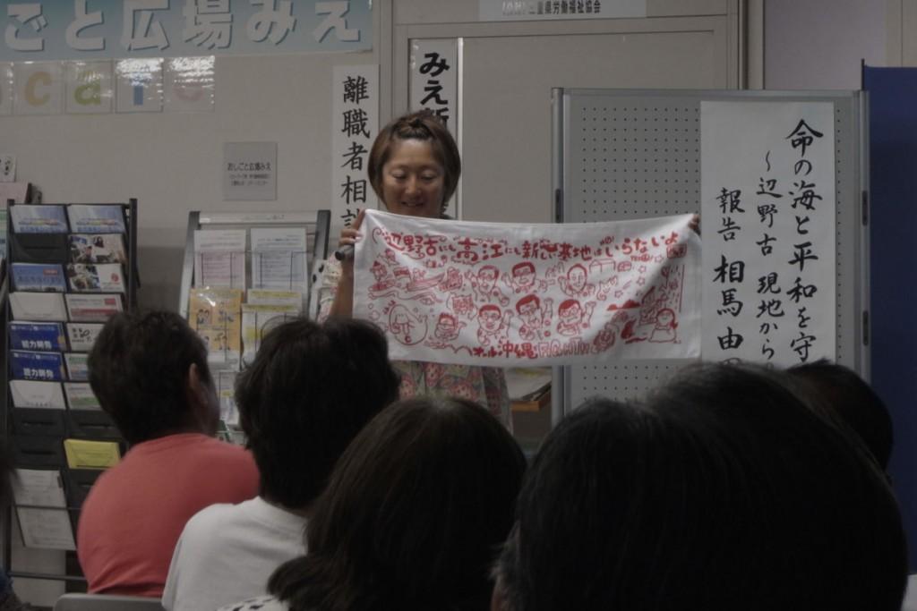 支援要請のタオルを掲げる相馬さん